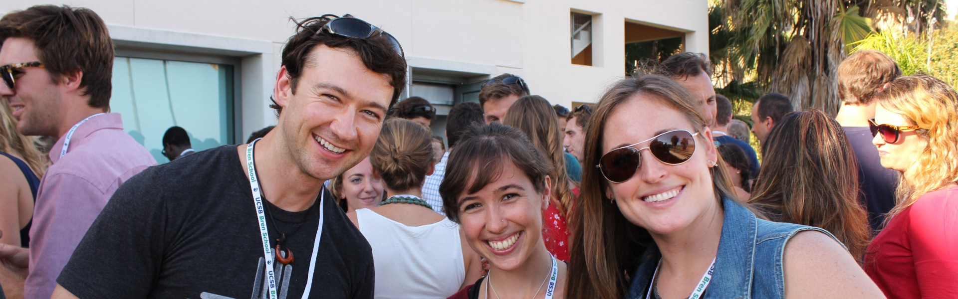 Three smiling people at an outdoor event