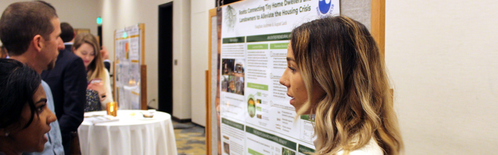 Woman standing by poster discussing with another woman