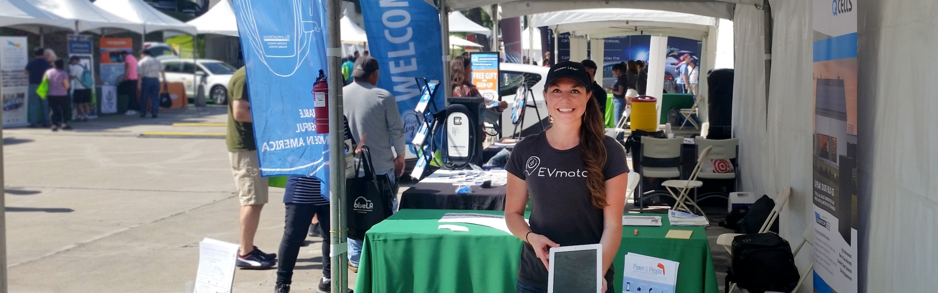 Woman holds tablet at booth at a community event