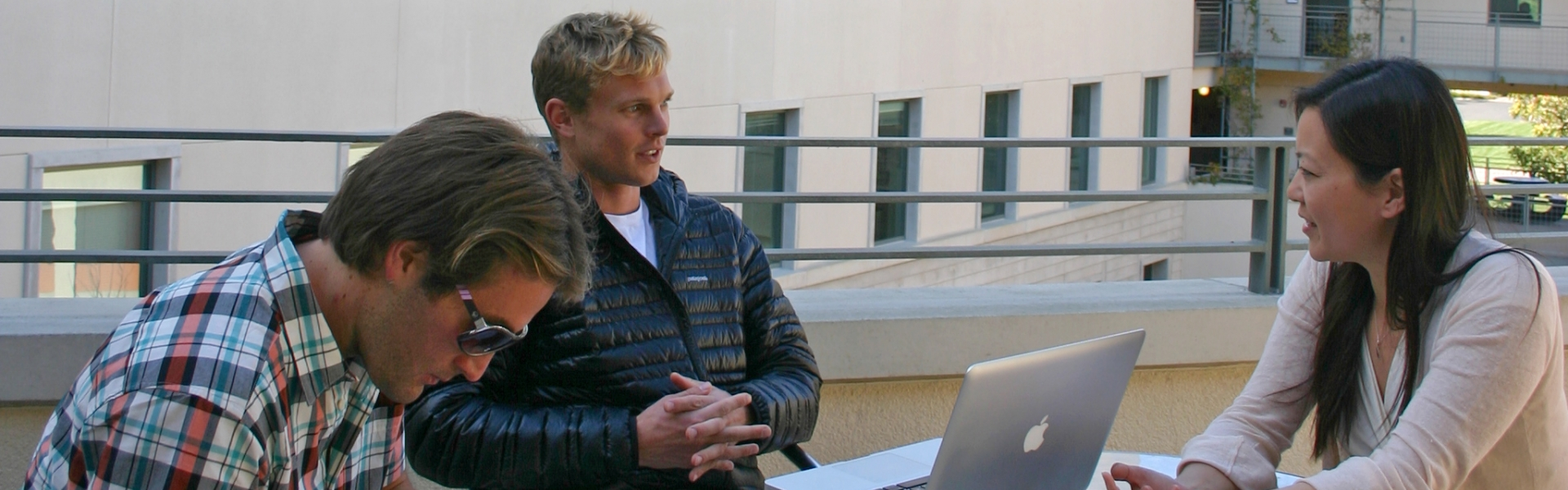 Two students with laptops having discussion with advisor