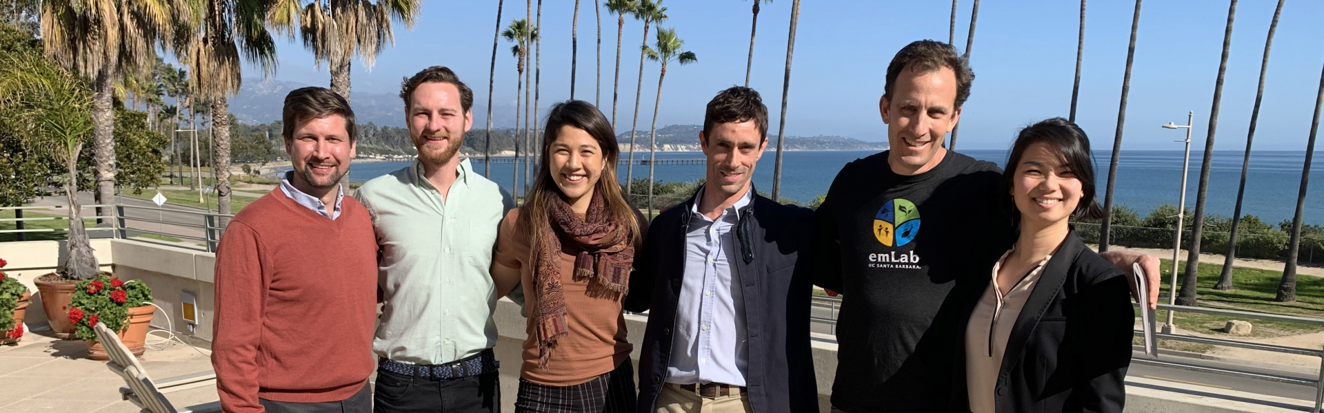 Five students stand with professor in group on terrace overlooking ocean