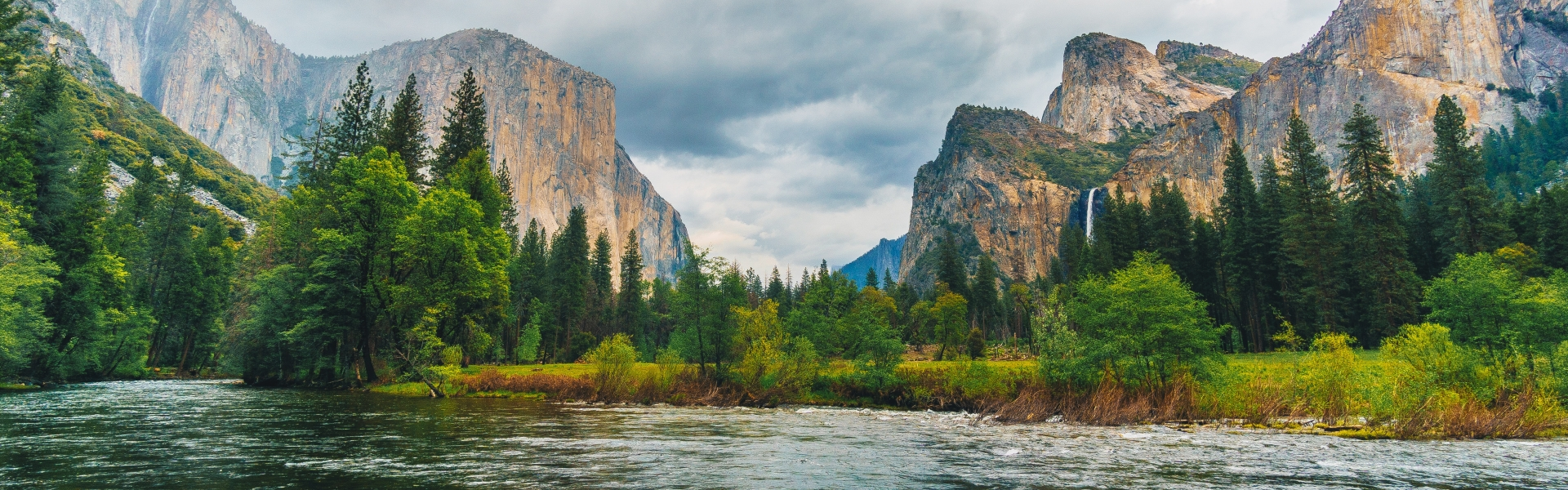 River flows by trees and Yosemite mountains