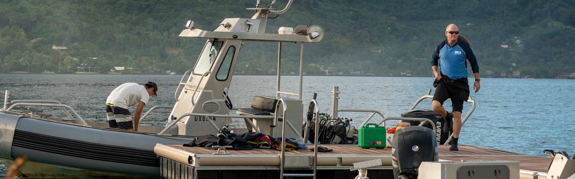 Two men gear up scuba equipment on a boat
