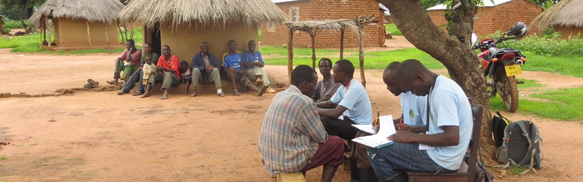 Group of Zambian farmers gathered on benches doing paperwork