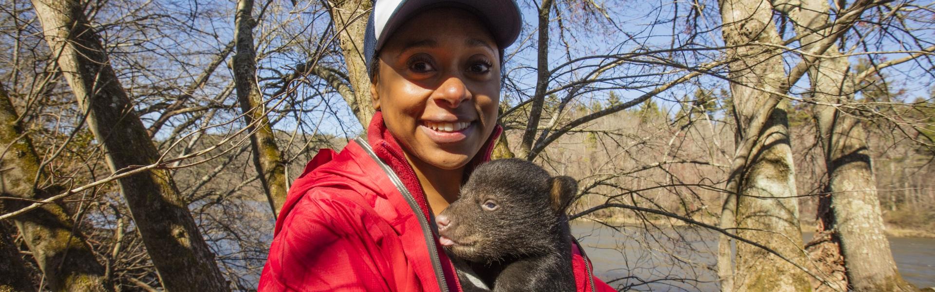 Dr. Rae Wynn-Grant holding a bear cub by a river