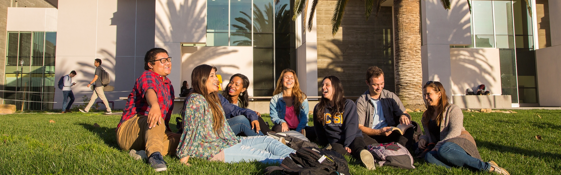 Seven students sitting in grass laughing