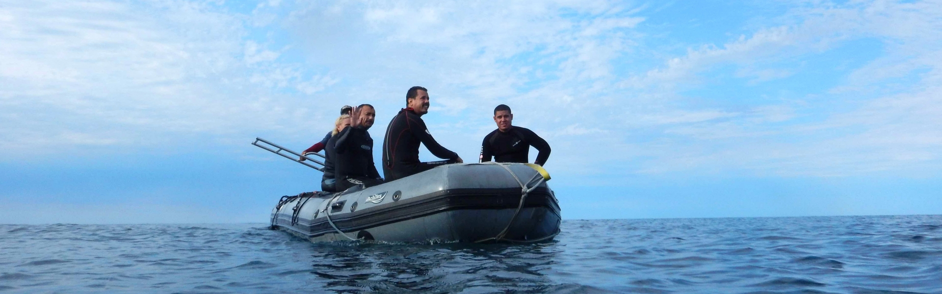 Four people in an inflatable boat on water