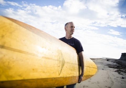 Man (Halpern) holding surfboard on the beach