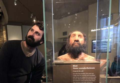 "Man places head next to model of ""neanderthal man"" at museum"