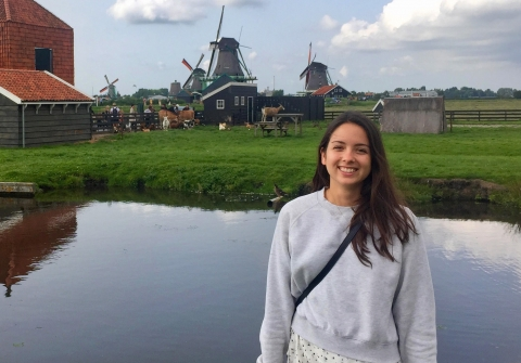 Woman stands in front of landscape with windmills and water