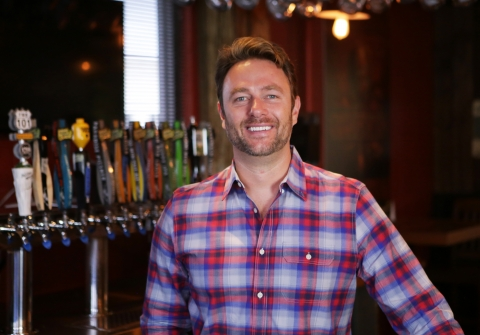 Smiling man in front of a beer tap
