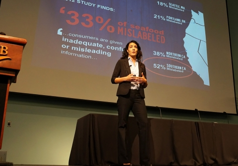 Woman stands on stage with seafood info projected on slide behind her