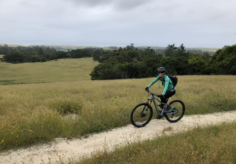Woman riding bicycle on dirt trail