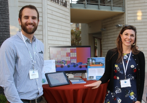 Two people stand by their media display at a tabling event