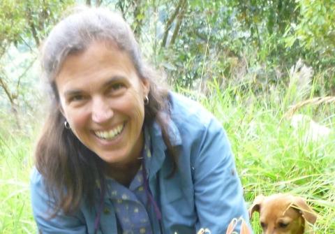 Karen Holl kneeling, planting a seedling