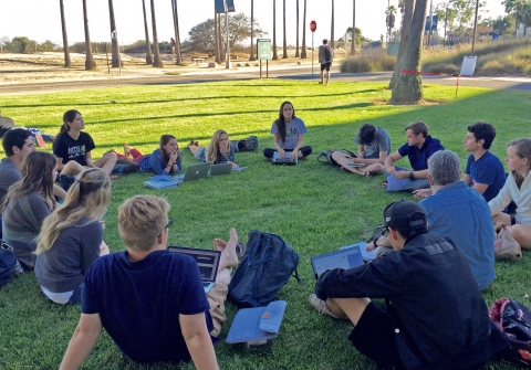 Group of students sitting in circle on grass