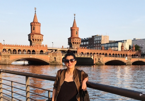 Woman standing on bridge overlooking urban river