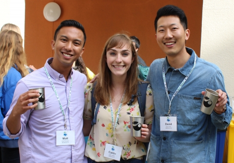 Three students smiling and holding up cups