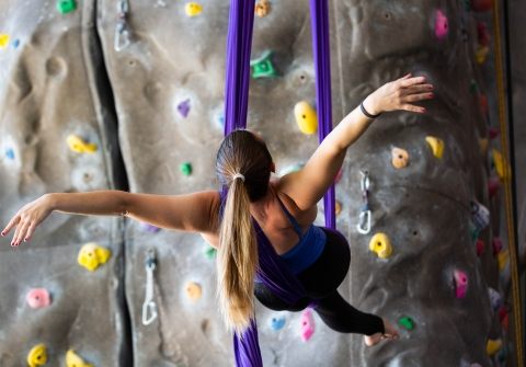 Woman does suspended acrobatics by climbing wall