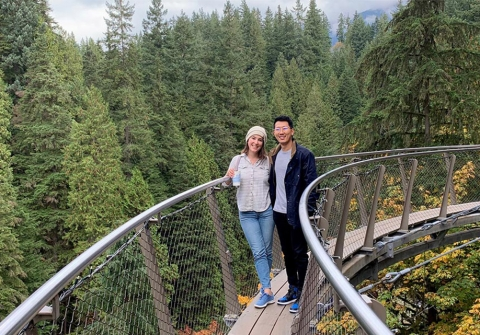 Woman and man stand on a suspended footbridge crossing a wooded area.
