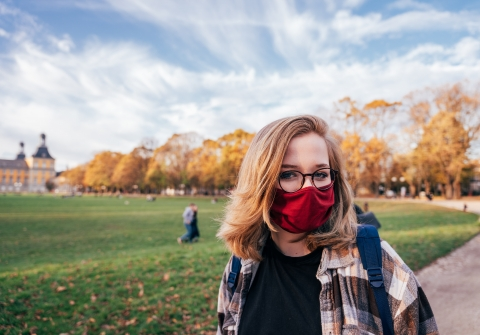 Woman on campus during fall wearing face mask