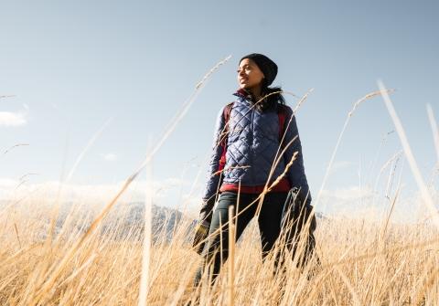 Dr. Rae Wynn-Grant standing in field of tall grass
