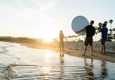 People on beach at sunset making a video