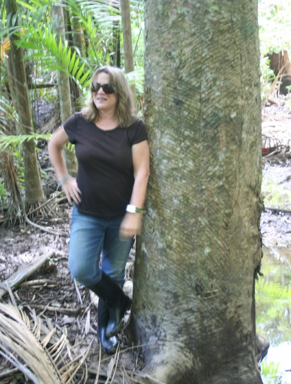 Susanna Hecht leans against a large tree trunk