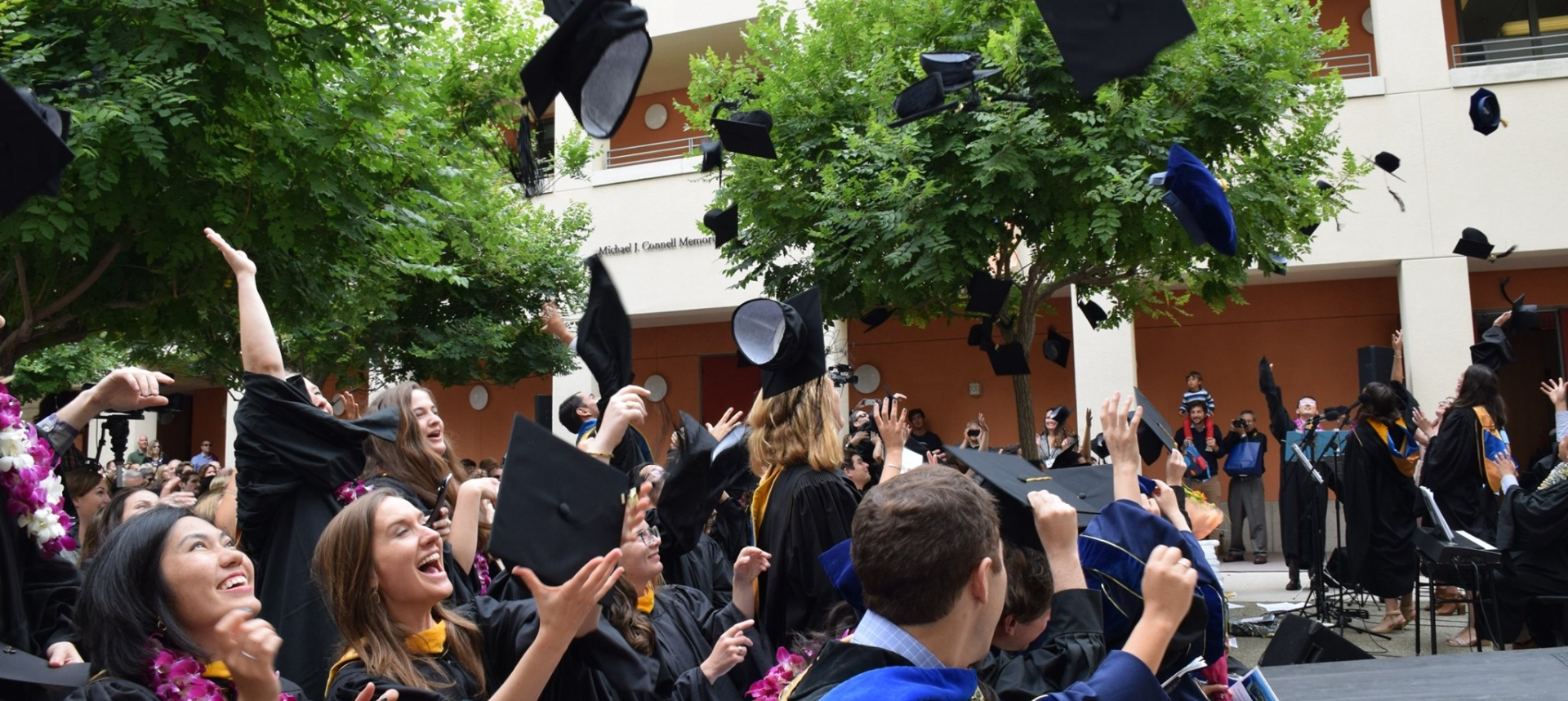 Grads throwing mortar board caps into the air