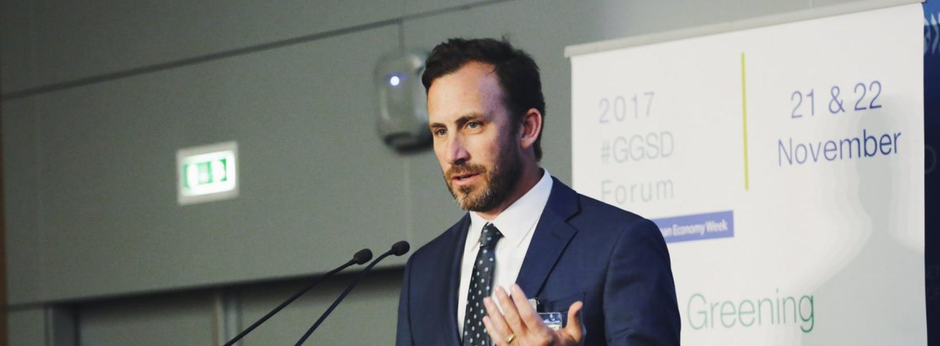 Man in a suit speaking at podium at GGSD Forum