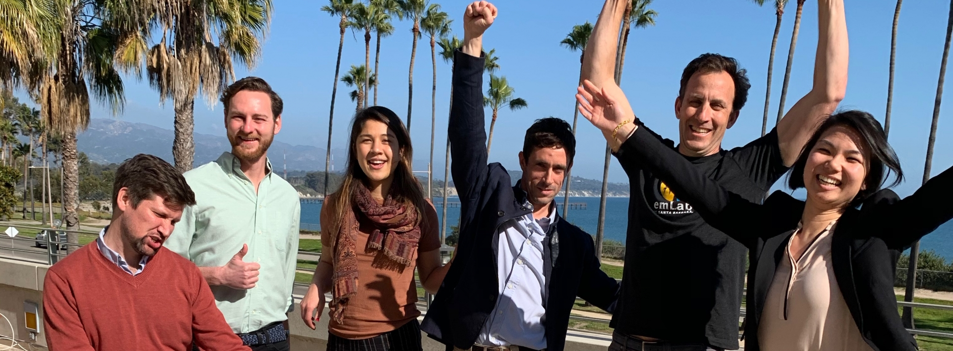 Six students cheering in happiness with ocean view