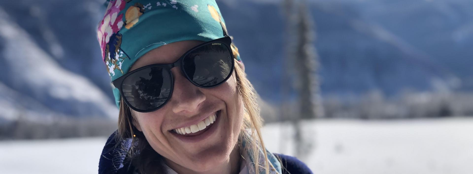 Smiling woman in sunglasses in snowy terrain