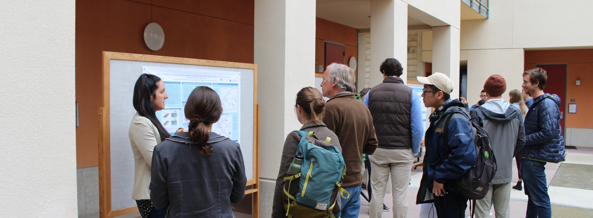 A student presents a poster in the Bren courtyard