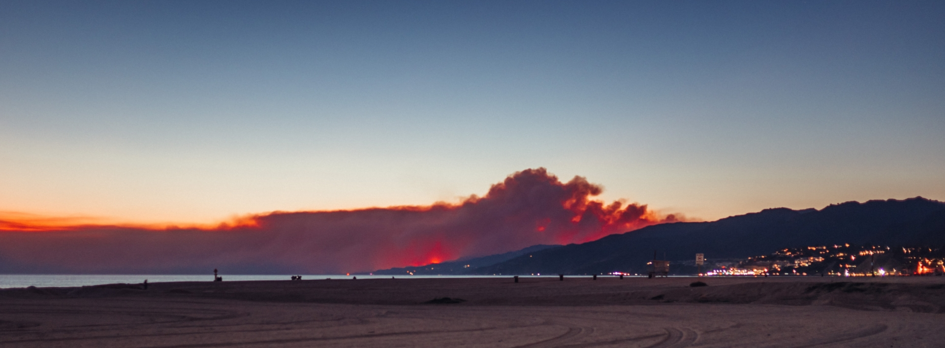 Wildfire smoke looms over hills of a seaside town