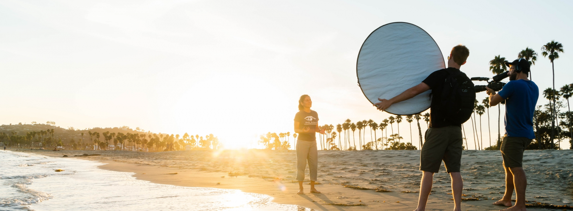 Video crew filming a woman talking on beach