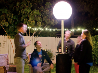 Four people sitting outdoors at night around a bright lamp