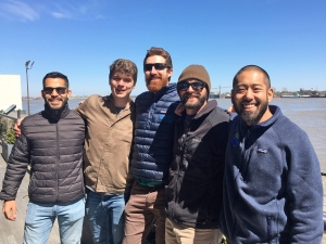 Five men in warm outdoor coats standing by sea shore