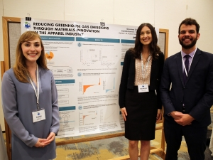 Three students standing in front of a project poster